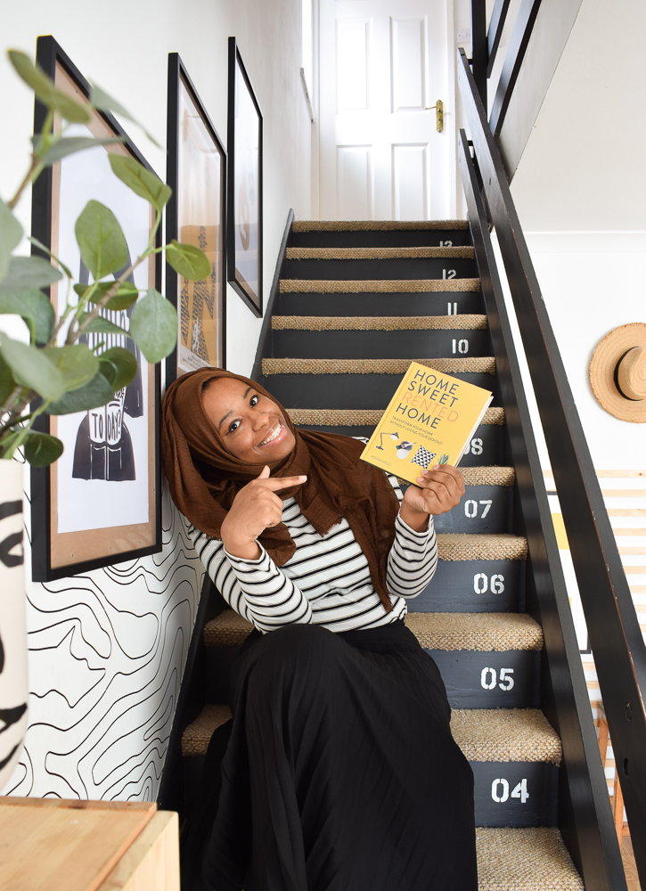 Medina Grillo holding her book and sitting on her stairs