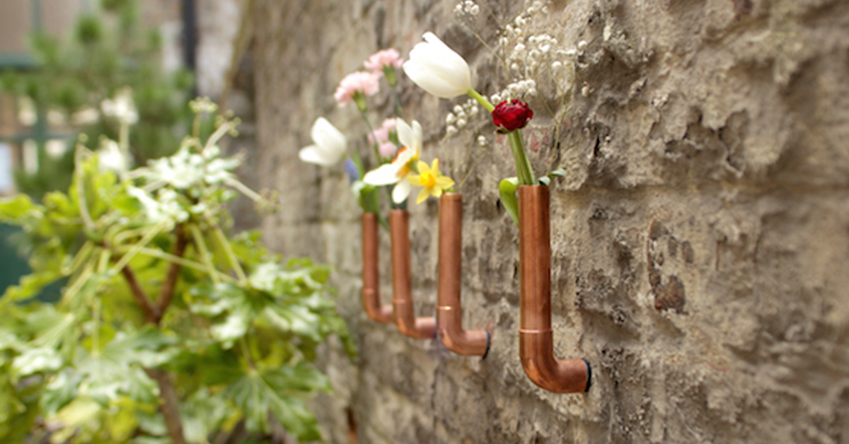 copper vases on a brick wall