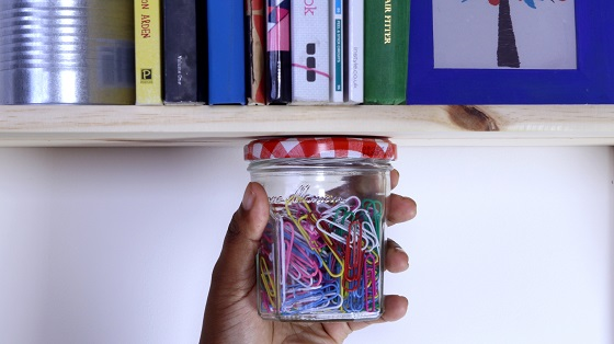 Hand holding jar hanging from shelf with Sugru